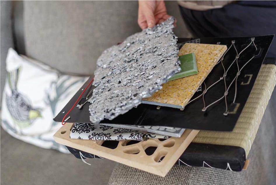 שרון אלה מומחית לחומרים מחזיקה בידה דוגמאות חומרים שונות בזמן יעוץ חומרים לאדריכלים