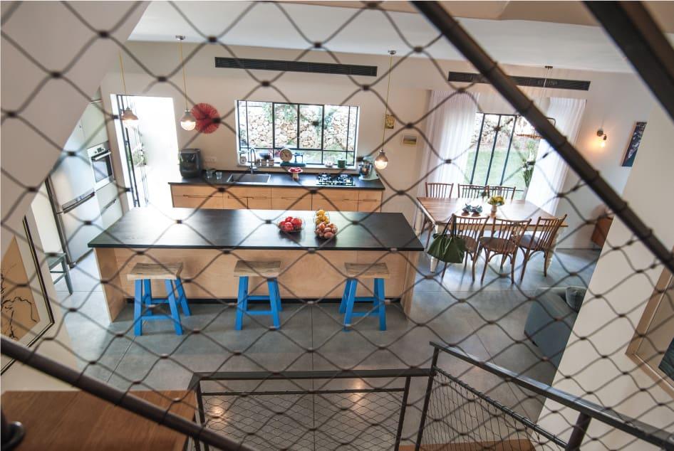 מבט למטבח בית פרטי בהרצליה ,דרך מעקה מדרגות המורכב ממסגרת ברזל וקשת נירוסטה נמתחת , רשת אקסטנדד , בתכנון ועיצוב שרון אלה