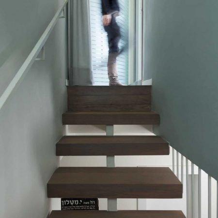 מעקה ברזל ומדרגות עץ אלון מלא המובילות לקומת חדר שינה הורים ומרפסות הגג