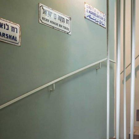 שלטי רחוב ישנים וינטג' על רקע קיר ירוק אפור במהלך מדרגות בדירת גג בתל אביב בעיצוב שרון אלה