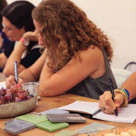 מעצבות פנים כותבות ולומדות במהלך שיעור בקורס ספריית החומרים של שרון