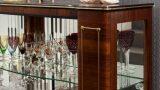 שידת וינטג' מקורית , עם אוספי כלים מקריסטל ופורצלן , על רקע קיר מחופה בטפט אפור , בבית פרטי בשכונת כרמליה בחיפה