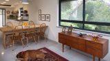 מבט לכיוון פינת האוכל והמטבח . רהיטי וינטג' מקוריים משולבים על רקע של רצפת סומסום , נוף הכרמל החיפאי ושטיח אותנטי ועליו שוכב הכלב
