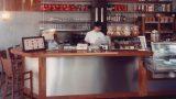 סניף קפה הלל בירושלים עם רצפת בטון מוחלקת, דלפק בחיפוי עץ מלא ומשטחי נירוסטה וקיר מחופה בלוחות בטון בעיצוב שרון אלה